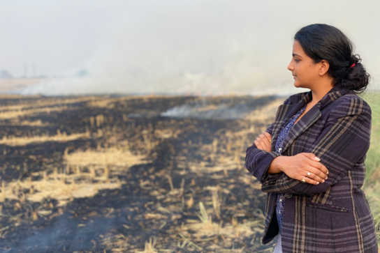 Craste founder Dr. Himansha Singh with a field of burning crops
