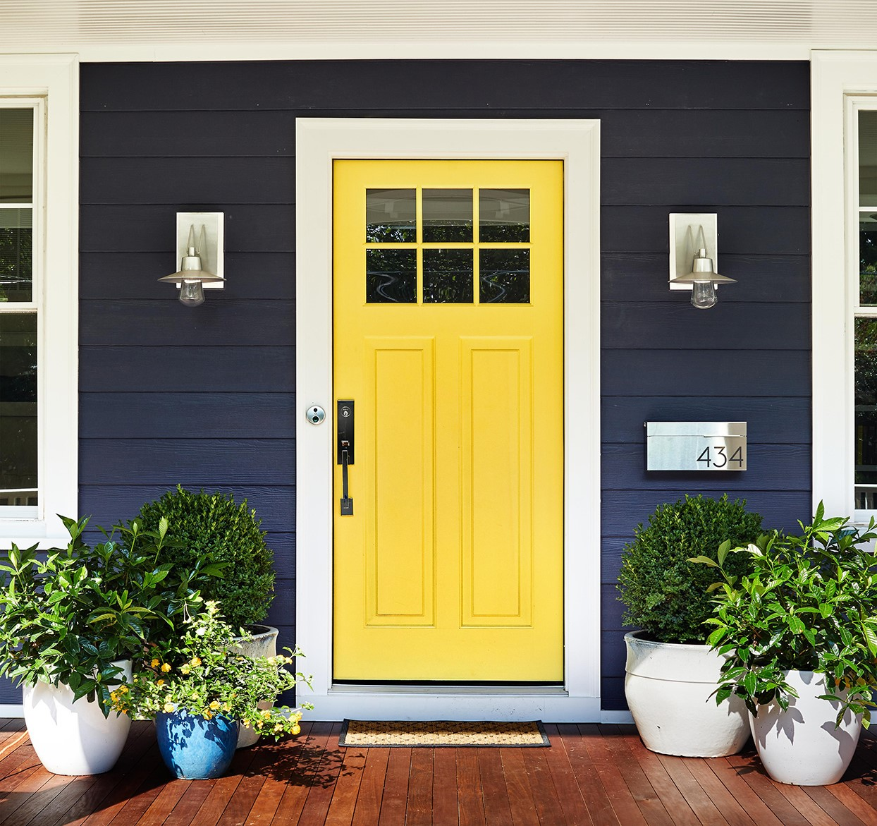 Bright yellow entry door on a blue home