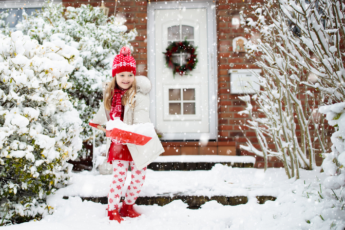 Young girl shoveling snow