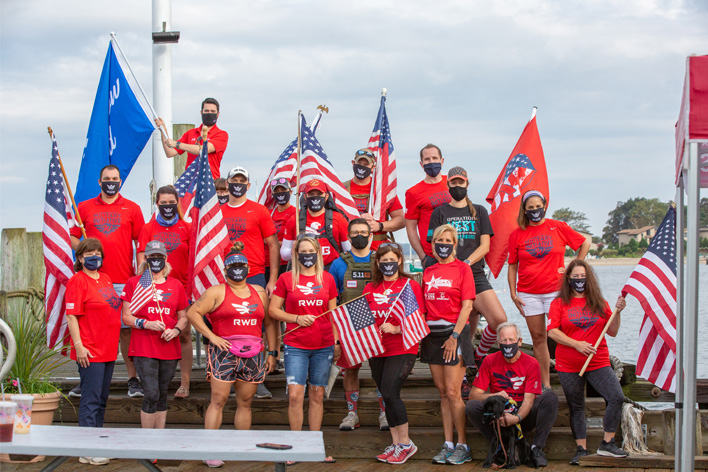 Group of Team RWB members and Window World employees posing with American flag