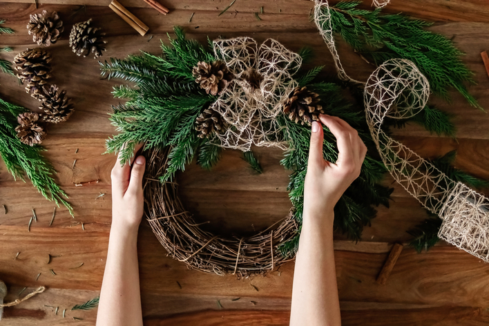 Hands making handmade bow on Christmas wreath