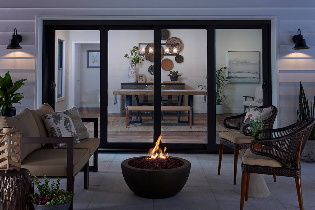 Outside living room with fireplace in front of big sliding doors