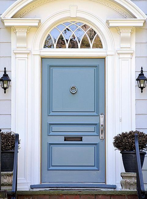 Light blue door on a light gray house.