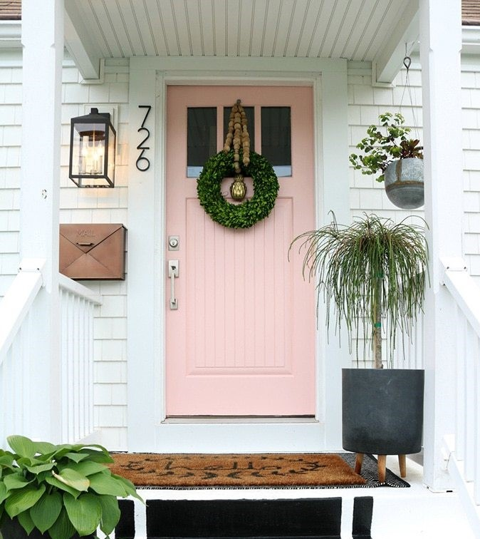 Coral-colored front door with white surround