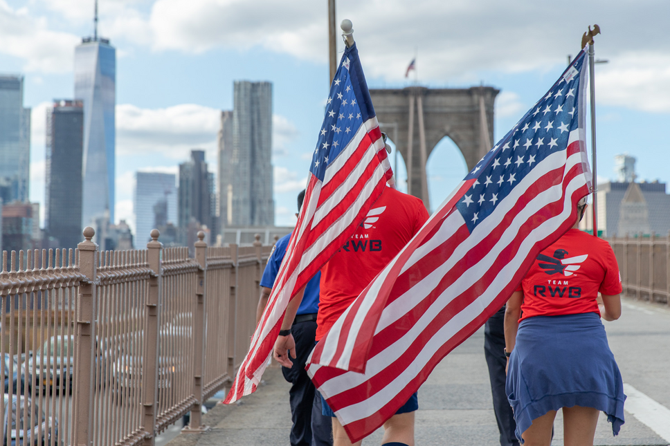 Supporters of Team Red, White, and Blue carry American Flags across a New York City bridge