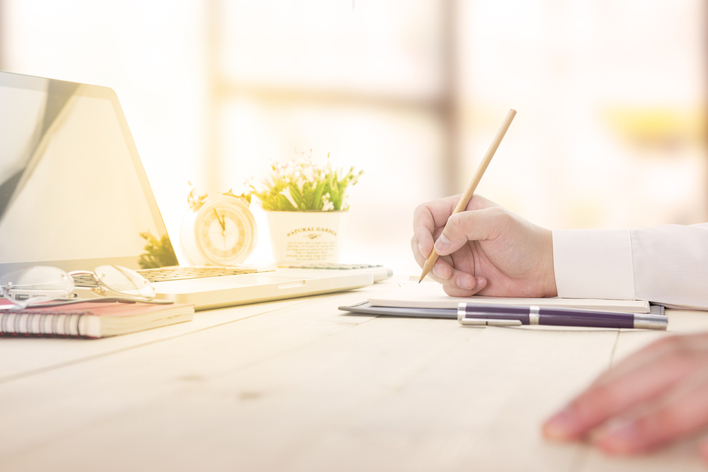 Man writing and planning at home desk