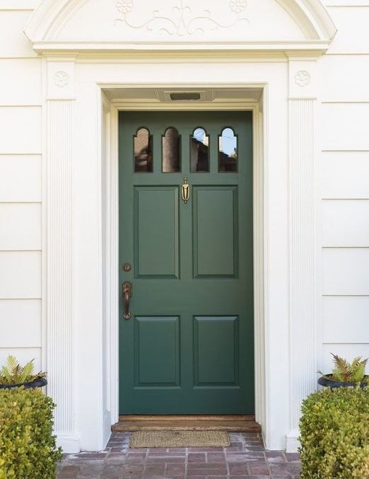 Dark green front door on a white house