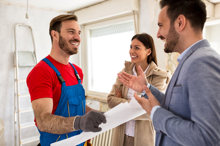 Contractor talking about details of home renovations to young smiling couple