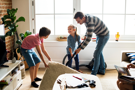 Dad and son cleaning living room together