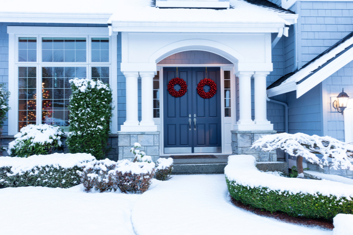 Red Christmas wreaths on a blue double front door