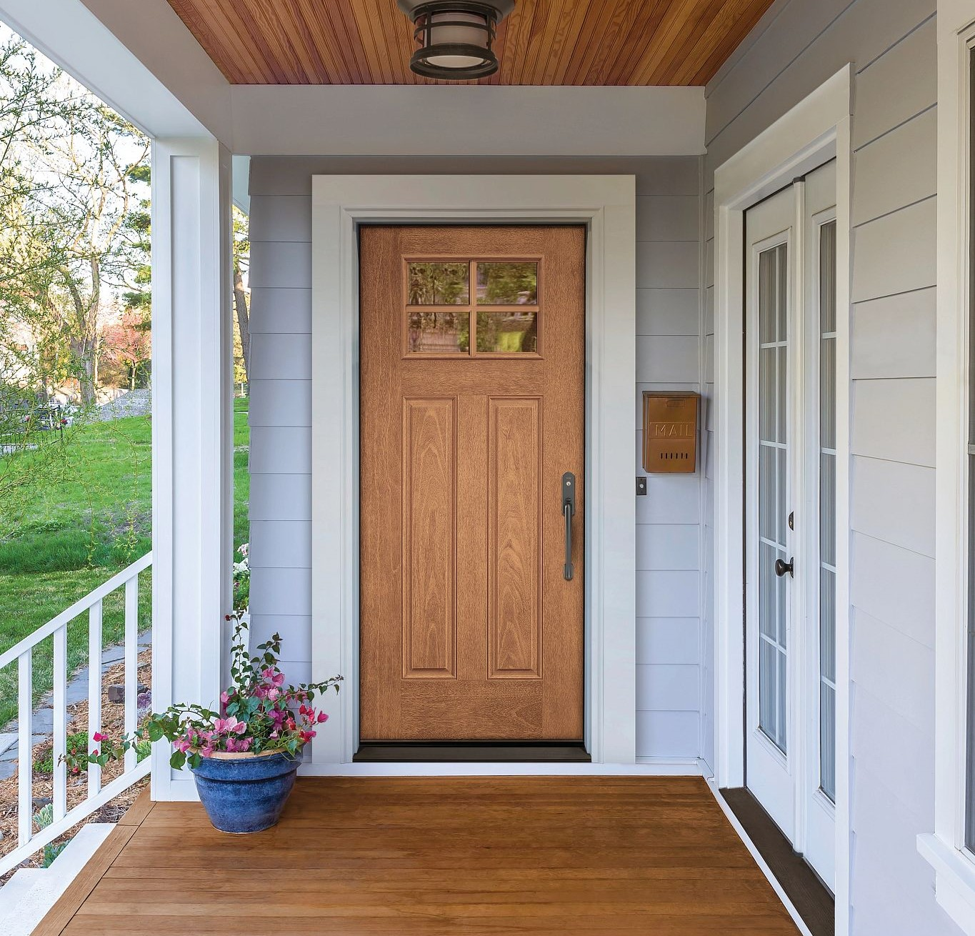 A light woodgrain door on a pastel front porch