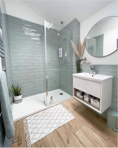 A green tile shower in a charming beach-inspired bathroom