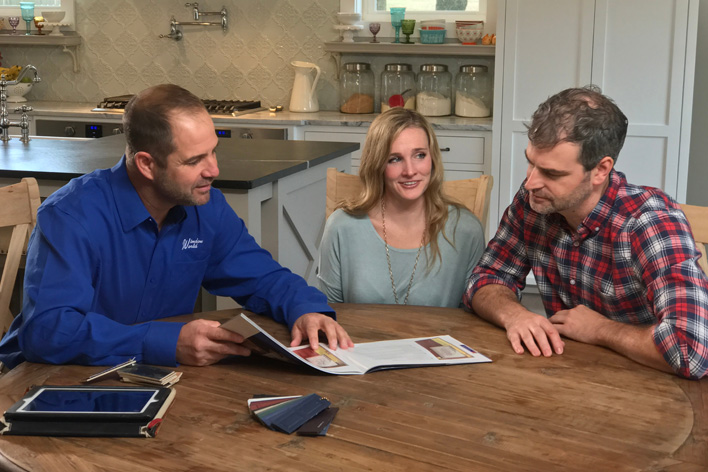 Happy couple sits with a professional contractor to discuss their home remodel