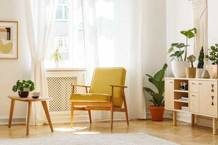 A mid-century modern yellow chair in a room with plants and other modern home design features