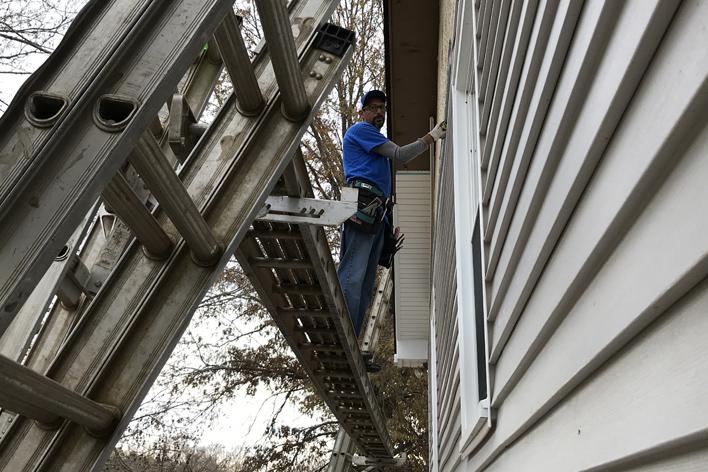 Man installing vinyl siding on a home