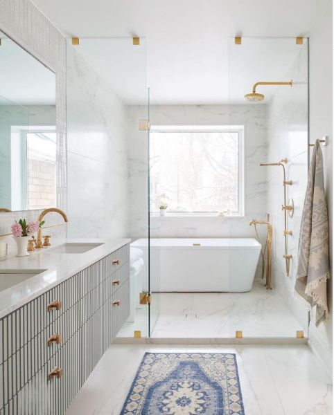 A beautiful bathroom with glass shower enclosure and brass hardware
