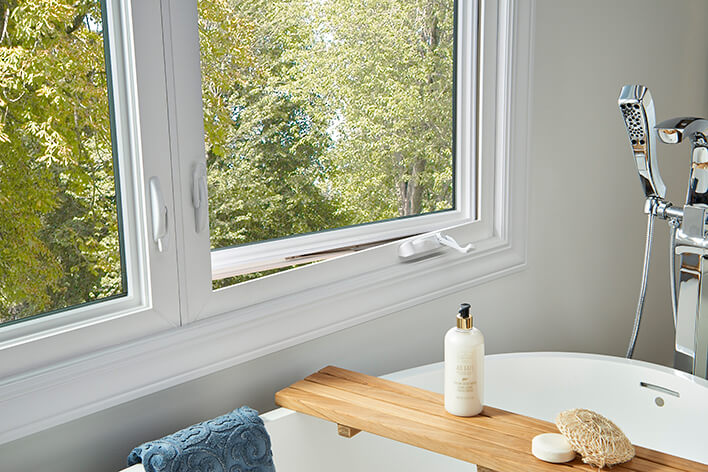 The bathroom of a ranch home is remodeled with casement windows beside the soaking tub
