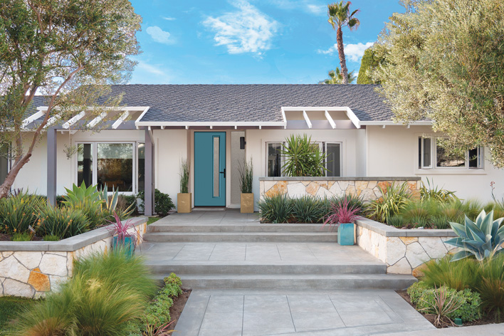 A mid-century modern home with exterior features that include a modern teal door and a linear landscape design