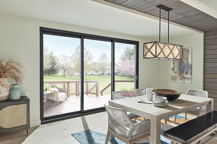 A dining room with a mid-century modern design and a sliding glass door on the back exterior of the home