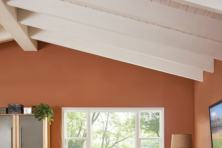 A vaulted ceiling with exposed beams in the living room is included in this ranch home remodel