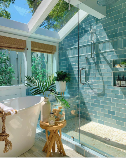 A nature-inspired bathroom with large windows, green tile, and many plants