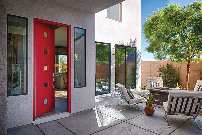 The exterior of a mid-century modern home that includes an outdoor living space and a modern red door
