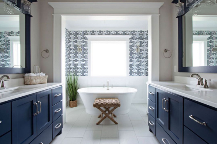 A large bathroom with matching blue vanities and white bathtub