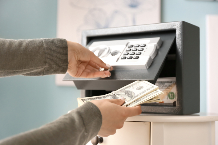 Woman putting money in a personal safe