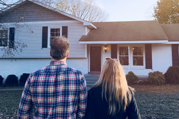 Man and woman looking at the exterior of a split-level home