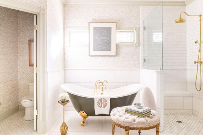 A large ornate bathroom with clawfoot tub and white design elements