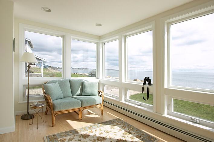 A sunroom with large casement windows providing beach views