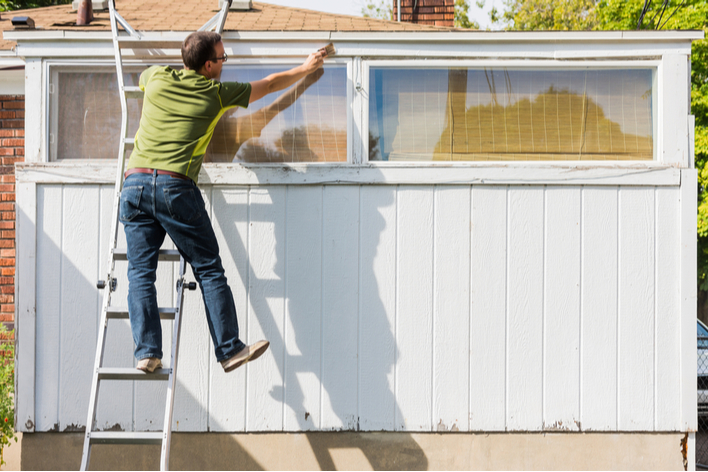 A man dangerously painting his house from a ladder
