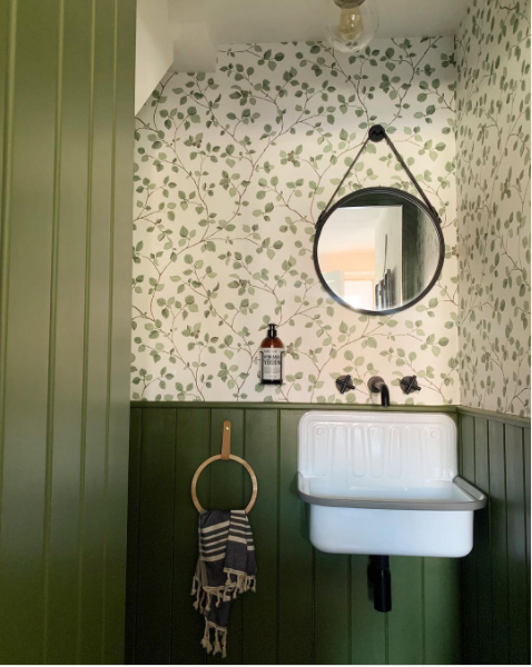 A unique green bathroom with stylish wallpaper and a circular mirror