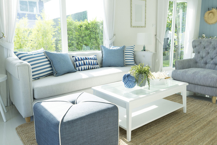 A living room in coastal tones and large windows
