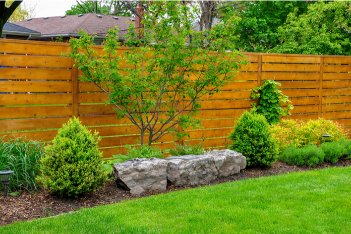 Fencing with horizontal lines, trees, and other landscaping features is used to update the exterior of a ranch-style house