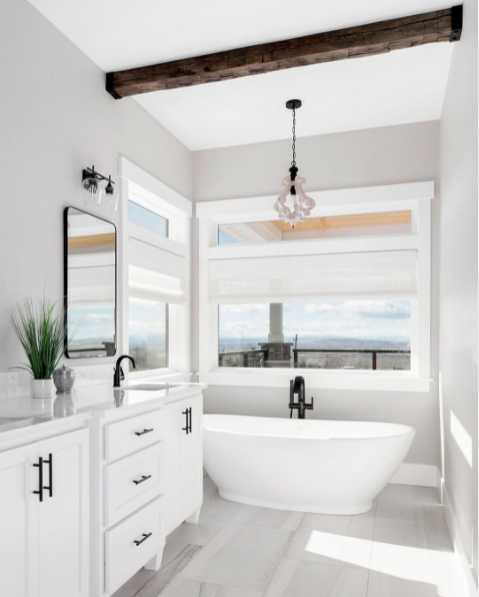 A charming bathroom with large windows, an exposed beam, and a comfy tub