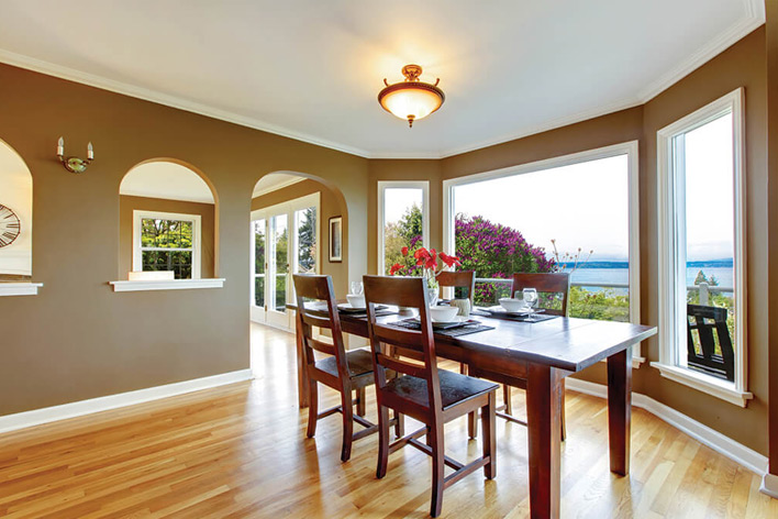 Dining area in a beach house with picture windows facing the beach