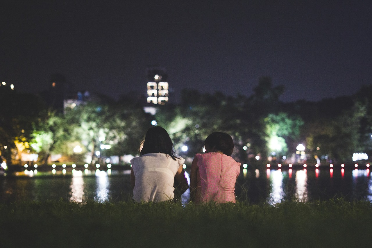 two people sitting by the waterfront