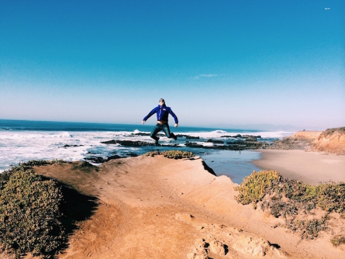man jumping on the sand by the coast