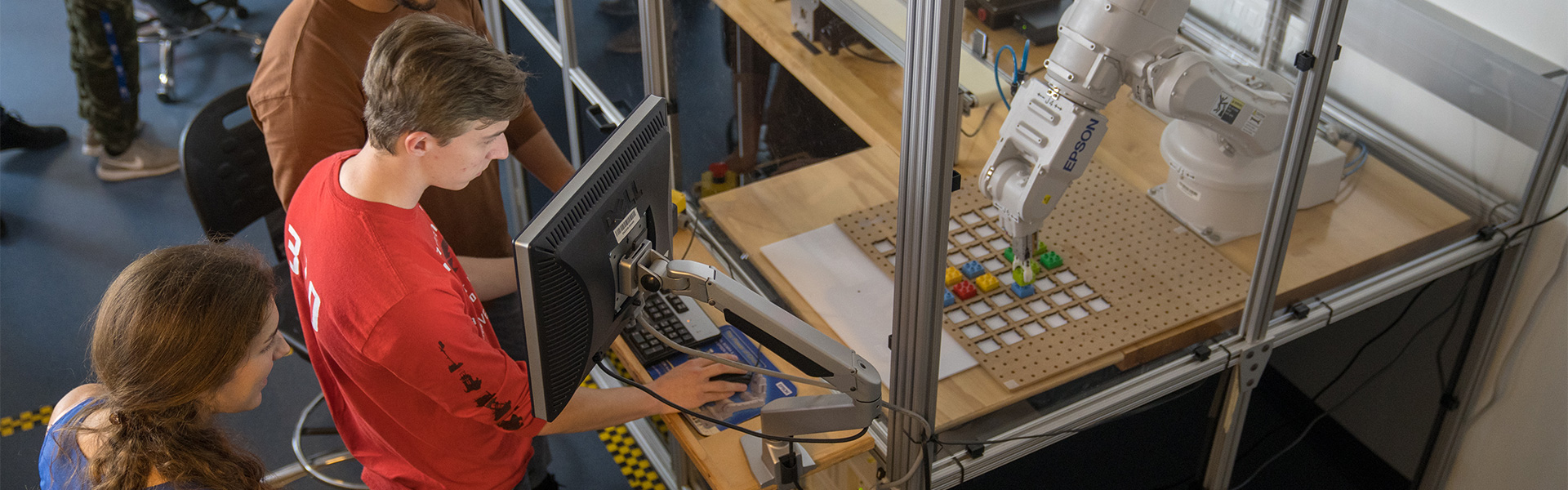Students working with a robotic arm in a mechatronics lab