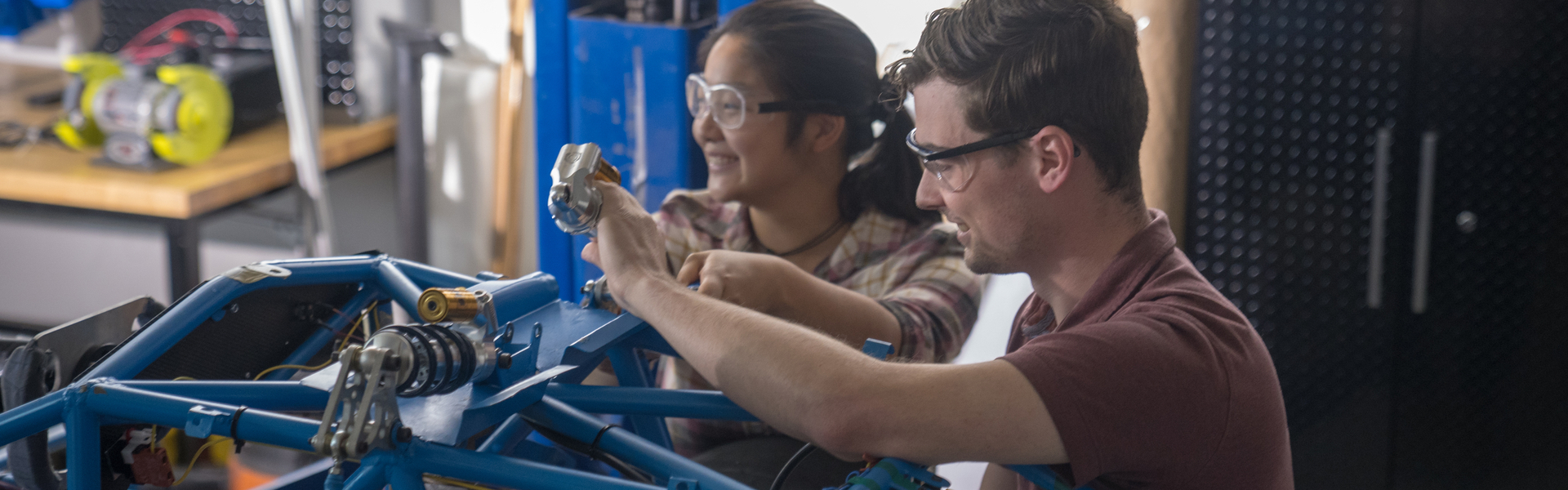 Male and female students working on a mechanical project in an engineering lab