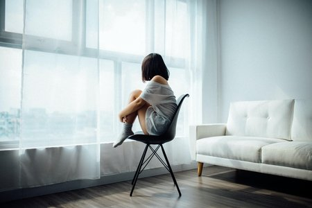 woman sitting alone looking out window