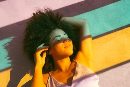 Black woman on floor colored color glass light lighting sun shine shining rainbow shadows