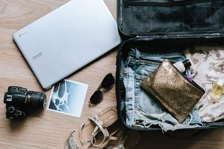 open suitcase with a laptop, camera, a photo, and sunglasses lying around it