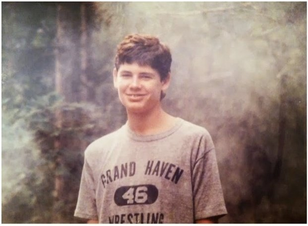 This is an image of a teen boy in front of a wooded background