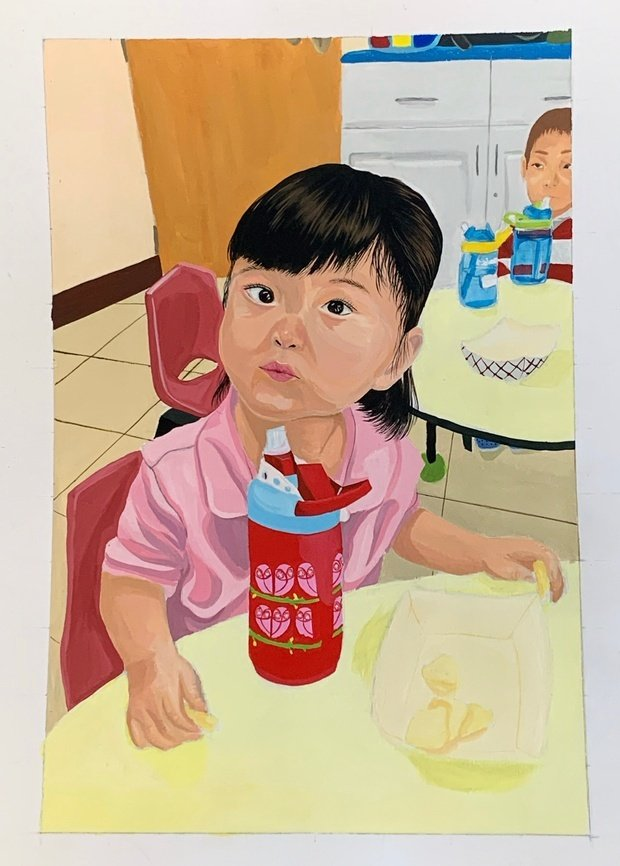 Little girl with a pink shirt sitting down with a red bottle on a yellow table and chips in her hand.