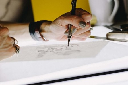 person letting on tracing paper using mechanical pencil