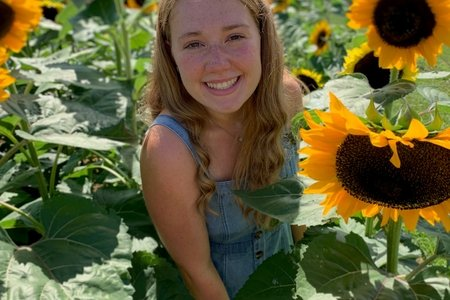 woman smiling with sunflowers