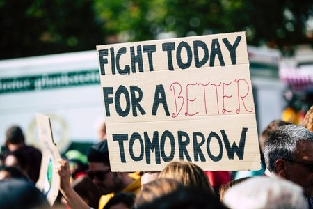 "cardboard sign being held up that says ""Fight Today For A Better Tomorrow"""
