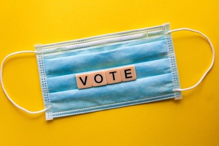 "blue mask with tiles spelling ""vote"" in front of yellow background."